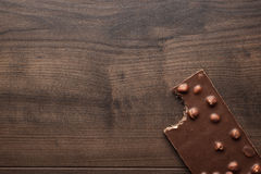 Nibbled chocolate bar with whole hazelnuts Royalty Free Stock Photography