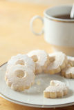 Nibbled italian Canestrelli biscuits near a cup of black tea Stock Photography