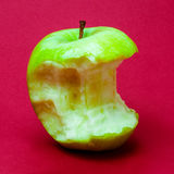 Nibbled wet green apple against red background 4 Stock Image