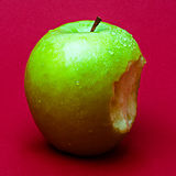 Nibbled wet green apple against red background 1 Stock Photography