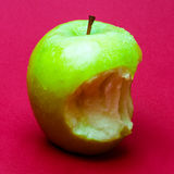 Nibbled wet green apple against red background 2 Royalty Free Stock Images
