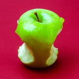 Nibbled wet green apple against red background 5 Stock Photo