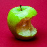 Nibbled wet green apple against red background 3 Royalty Free Stock Photos