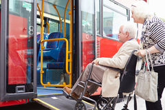 Ônibus superior do embarque dos pares usando a rampa de acesso da cadeira de rodas Imagens de Stock