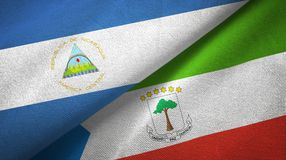 Nicaragua and Equatorial Guinea two flags textile cloth, fabric texture. Nicaragua and Equatorial Guinea two folded flags together royalty free stock image