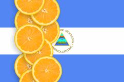 Nicaragua flag and citrus fruit slices vertical row. Nicaragua flag and vertical row of orange citrus fruit slices. Concept of growing as well as import and royalty free illustration