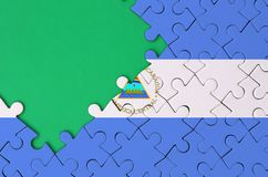 Nicaragua flag is depicted on a completed jigsaw puzzle with free green copy space on the left side.  stock illustration