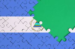 Nicaragua flag is depicted on a completed jigsaw puzzle with free green copy space on the right side.  stock photography