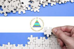 Nicaragua flag is depicted on a table on which the human hand folds a puzzle of white color.  royalty free stock image