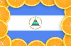 Nicaragua flag in fresh citrus fruit slices frame. Nicaragua flag in frame of orange citrus fruit slices. Concept of growing as well as import and export of stock photos