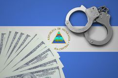 Nicaragua flag with handcuffs and a bundle of dollars. The concept of illegal banking operations in US currency.  royalty free stock photos