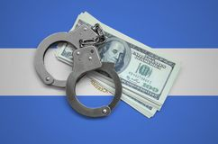 Nicaragua flag with handcuffs and a bundle of dollars. Currency corruption in the country. Financial crimes.  royalty free stock image
