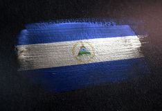 Nicaragua Flag Made of Metallic Brush Paint on Grunge Dark Wall.  royalty free stock photography