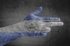 Nicaragua flag painted on male hand like a gun. Isolated on concrete background royalty free stock image