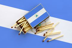 Nicaragua flag is shown on an open matchbox, from which several matches fall and lies on a large flag.  royalty free stock photo