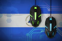 Nicaragua flag and two mice with backlight. Online cooperative games. Cyber sport team. Nicaragua flag and two modern computer mice with backlight. The concept royalty free stock photo