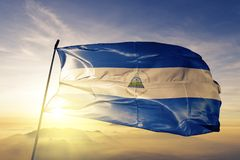 Nicaragua national flag textile cloth fabric waving on the top. Sunrise mist fog royalty free stock photo