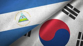 Nicaragua and South Korea two flags textile cloth, fabric texture. Nicaragua and South Korea flags together textile cloth, fabric texture stock photography