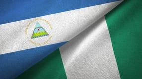 Nicaragua- und Nigeria-zwei Flaggentextilstoff, Gewebebeschaffenheit lizenzfreies stockfoto