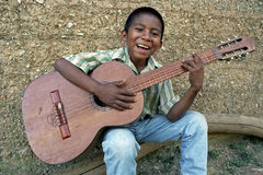 Nicaraguan Boy playing on his guitar, Nicaragua. In the city, the capital, Managua: a boy for his home is to make music on his guitar. Music is in the blood of Stock Photo