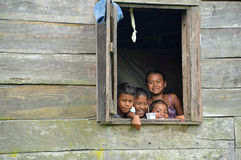 Nicaraguan children in window. SAUPUKA, NICARAGUA - JULY 8, 2015: Three unknown Nicaraguan girls and one unknown Nicaraguan smiling from the window of their home royalty free stock photos