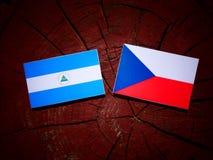 Nicaraguan flag with Czech flag on a tree stump. Nicaraguan flag with Czech flag on a tree stump Stock Photos
