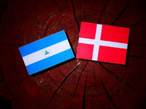 Nicaraguan flag with Danish flag on a tree stump isolated. Nicaraguan flag with Danish flag on a tree stump Stock Photo