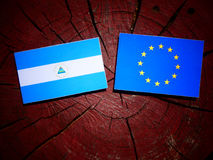 Nicaraguan flag with EU flag on a tree stump isolated. Nicaraguan flag with EU flag on a tree stump Stock Images