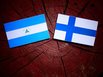 Nicaraguan flag with Finnish flag on a tree stump isolated. Nicaraguan flag with Finnish flag on a tree stump Stock Photography