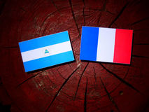 Nicaraguan flag with French flag on a tree stump isolated. Nicaraguan flag with French flag on a tree stump Royalty Free Stock Image