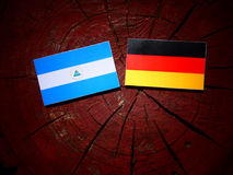 Nicaraguan flag with German flag on a tree stump. Nicaraguan flag with German flag on a tree stump Royalty Free Stock Images