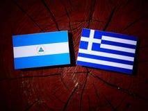 Nicaraguan flag with Greek flag on a tree stump isolated. Nicaraguan flag with Greek flag on a tree stump Stock Photo