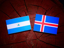 Nicaraguan flag with Icelandic flag on a tree stump isolated. Nicaraguan flag with Icelandic flag on a tree stump Royalty Free Stock Photo