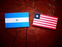 Nicaraguan flag with Liberian flag on a tree stump isolated. Nicaraguan flag with Liberian flag on a tree stump Stock Photography