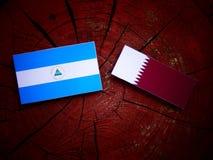 Nicaraguan flag with Qatari flag on a tree stump isolated. Nicaraguan flag with Qatari flag on a tree stump Stock Photography