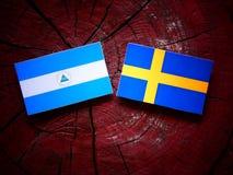 Nicaraguan flag with Swedish flag on a tree stump. Nicaraguan flag with Swedish flag on a tree stump Stock Image