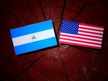Nicaraguan flag with USA flag on a tree stump. Nicaraguan flag with USA flag on a tree stump Stock Image