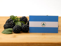 Nicaraguan flag on a wooden panel with blackberries isolated on. A white background Royalty Free Stock Images