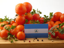 Nicaraguan flag on a wooden panel with tomatoes isolated on a wh. Ite background Stock Images