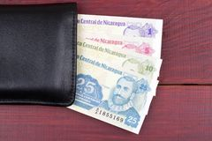 Nicaraguan money in the black wallet. On a wooden background Stock Photo