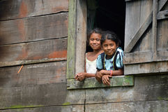 Nicaraguan sister. SAUPUKA, NICARAGUA - JULY 8, 2015: Two school age, unknown Niaraguan girls looking outside from their house window, as I, the rare tourist Stock Photography