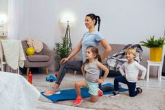 Nice active children sitting on one knee. Sports activities. Nice active children sitting on one knee while repeating after their mother royalty free stock images