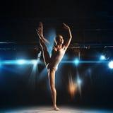 Nice adult ballerina posing on stage of theater Stock Photos