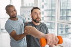 Nice adult man doing a physical exercise. Physical rehabilitation. Nice pleasant adult men doing a physical exercise while being helped by his therapist stock photo