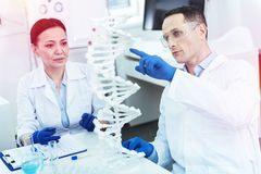 Nice adult man pointing at the DNA model. Look there. Nice adult men pointing at the DNA model while talking to his colleague royalty free stock photo