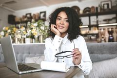 Nice African American girl working in restaurant with laptop and notebook. Pretty girl sitting at cafe with glasses in stock image