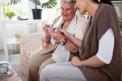 Nice afternoon with granddaughter. Grandmother reading article on smartphone with her granddaughter Royalty Free Stock Photo