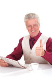 Nice aged man sits at a table with a newspaper Stock Image