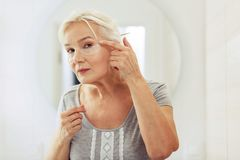 Nice aged woman putting eye patches on her face. Perfect look. Nice aged woman putting eye patches on her face while standing in front of the window stock photography