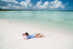 Nice amazing gorgeous view of a little girl lying on white sand beach Stock Image